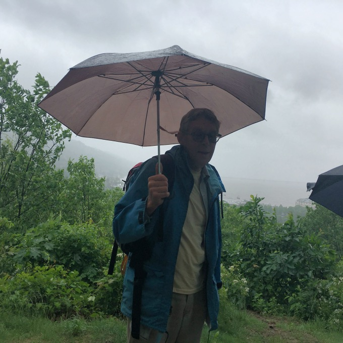 NY Ramblers hike leader, Chris, holding umbrella in front of cloudy rainy sky.