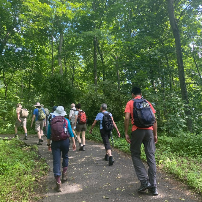 NYC hiking group walking up paved walkway approaching park woods.