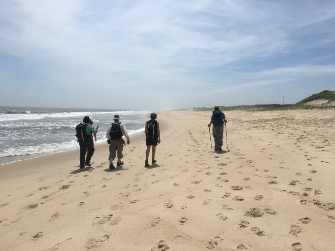 NYC hiking group, the New York Ramblers, hiking on beach at water's edge.