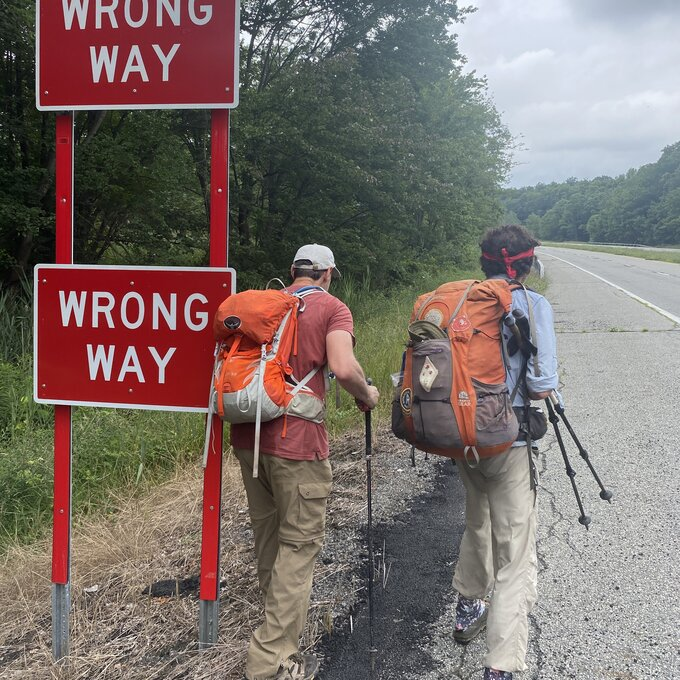 """Photo of NYC hiking group walking past """"Wrong Way"""" signs on highway."""