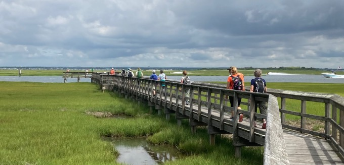 New York City hiking group walking out onto wooden pier extending out into salt marsh.