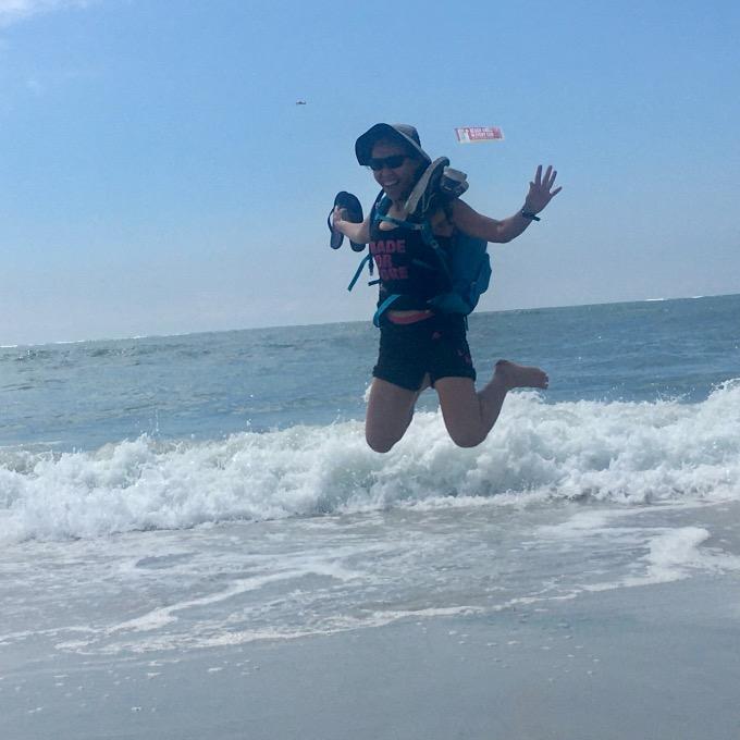 New York Rambler hiker jumping into the air above ocean surf.