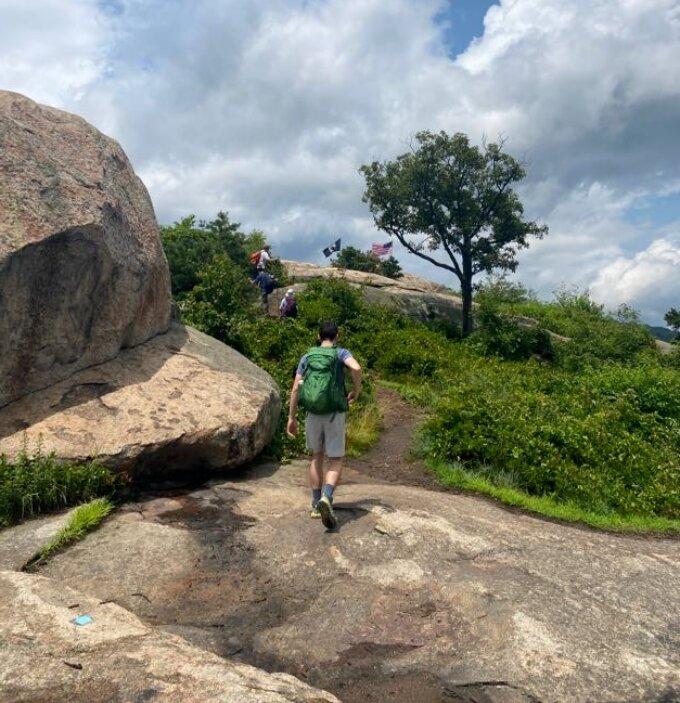 Photo of hikers walking up rock slabs on Popolopen Torne.